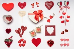 Various hearts and stylish accessories in heart shape, gifts and sweets in red color on white background. Empty photoframe, mock up. Greeting card for Valentine's day, love and romance concept