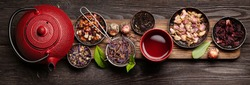 Various herbal dry tea, teapot and cup on wooden table. Top view flat lay
