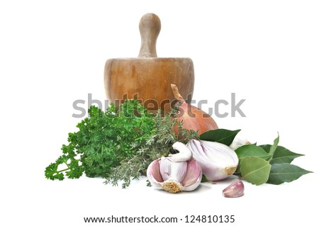 various herbs and onions and garlic with a wooden pestle isolated