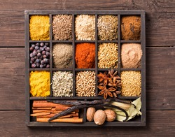 Various herbs and powder spices in box on old wooden background top view.