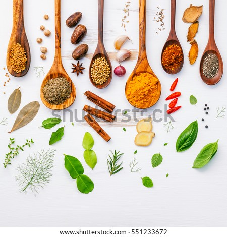 Shutterstock Various herbs and spices in wooden spoons. Flat lay of spices ingredients chilli ,pepper, garlic,dries thyme, cinnamon,star anise, nutmeg,rosemary, sweet basil and kaffir lime on wooden background.