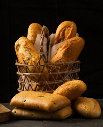 Various homemade bread loaves, some inside the wicker basket, and others arranged around it, all shot against a black background.
