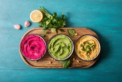 Various hummus dips, flat lay of hummus in different colours with spinach, beetroot and vegetables, vegan snack