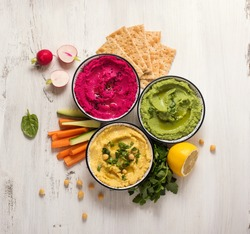 Various hummus dips, flat lay of hummus in different colours with spinach, beetroot and vegetables, healthy vegan snack