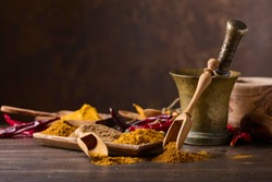 Various Indian spices with wooden spoons on a old wooden table, copy space for  your content.
