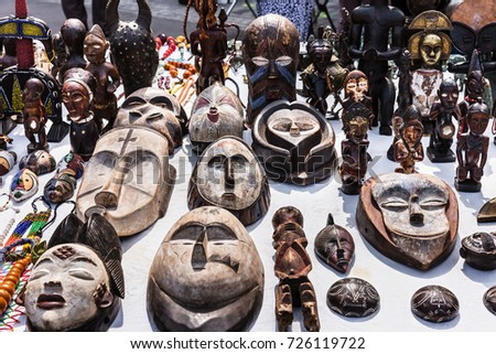various interesting wooden masks and figures of african culture on sale at the flea market in