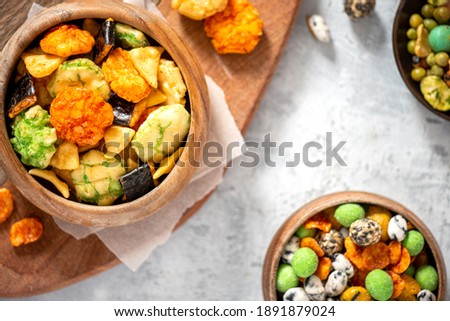 Various Japanese snacks in a wooden bowl close-up. Rice crackers with wasabi and nori, peanuts with sesame seeds, and other snacks. Mix traditional Japanese snack food.