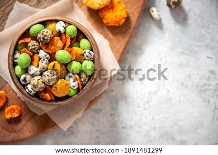 Various Japanese snacks in a wooden bowl on a grey background. Free space for text. Rice crackers with wasabi and nori, peanuts with sesame seeds, and other snacks.  Mix traditional Japanese snack