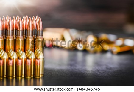 Various kind of bullets or ammonution on dark stone table. Bullet pile in war ammo background. Magazines, rounds and military technology. Wide banner or panorama guns photo.