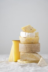 Various kind of cheese served on wooden board, traditional pieces of Spanish, French, Italy cheese. Light background with copy space, table with gray linen tablecloth