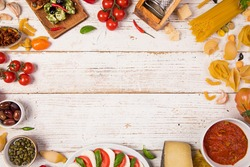 Various kind of italian food served on vintage wooden table. Top view, free space for text