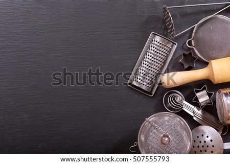 Various kitchen utensils on dark background, top view #507555793