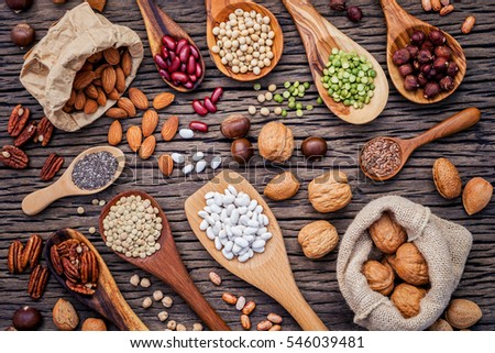 Various legumes and different kinds of nutshells in spoons. Walnuts kernels ,hazelnuts, almond ,brown pinto ,soy beans ,flax seeds ,chia ,chickpea ,red kidney beans and pecan on shabby wooden table. #546039481