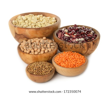 Various legumes in wooden bowl isolated on white background