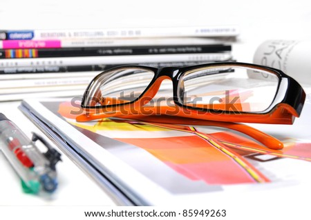 Various magazines with orange colored glasses and ball pen on white background