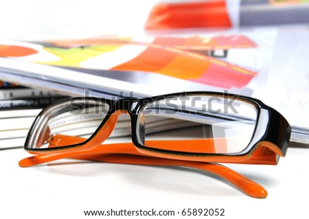 Various magazines with orange colored glasses over white background