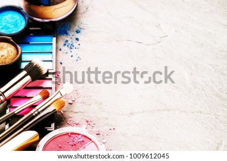 Various makeup products on dark background with copyspace. Beauty and fashion concept