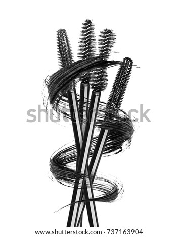 Various mascara brushes wrapped in a smear in the shape of a spiral, isolated on white background