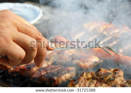 various meat grilled on barbecue in smoke closeup