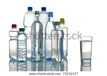 various mineral water bottles and full glass isolated