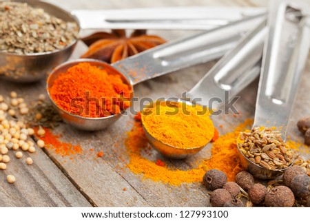 Various mixed spices (oregano, curcuma, paprika, anise) in metal scoops on wooden table