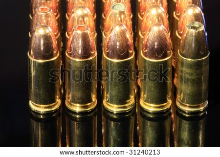 Various 9mm bullets isolated on a black reflective surface