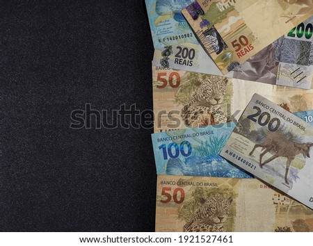 various money notes of 50 reais 100 reais and 200 reais from brazil on a black background. space for text. money from brazil. earn money. Real, Currency, Money, Dinheiro, Reais, Brasil.