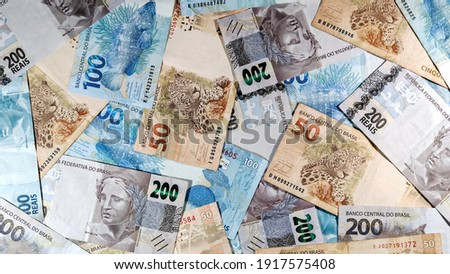 various money notes of 50 reais 100 reais and 200 reais from brazil on a wood background. space for text. money from brazil. earn money. Real, Currency, Money, Dinheiro, Reais, Brasil.