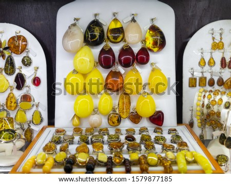 Various natural amber necklaces, earrings and pendants in glass case of jewelry store #1579877185