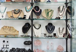 Various natural semiprecious stone jewelry in glass case of jewelry store