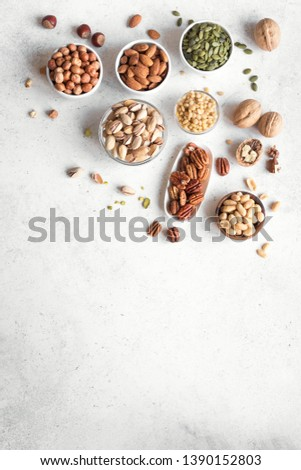 Various Nuts in  bowls on white background, top view, copy space. Nuts assortment frame - pecans, hazelnuts, walnuts, pistachios, almonds, pine nuts, peanuts, pumpkin seeds.