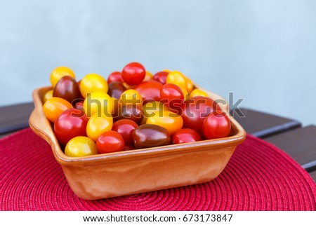 Various of colorful cherry tomatoes in a ceramic bowl. Healthy eating or vegetarian concept. #673173847