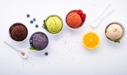 Various of ice cream flavor ball blueberry ,lime ,pistachio ,almond ,orange ,chocolate and vanilla set up on white wooden background . Summer and Sweet menu concept.