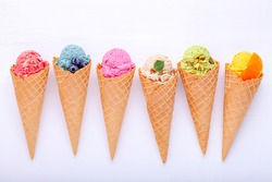 Various of ice cream flavor in cones blueberry ,strawberry ,pistachio ,almond ,orange and cherry setup on white wooden background . Summer and Sweet menu concept.