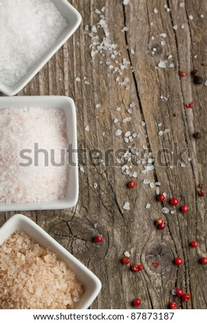 Various of salt and pepper on old wooden table as background