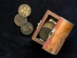 Various old, well-used South African pennies in a small wooden treasure chest on a Black background