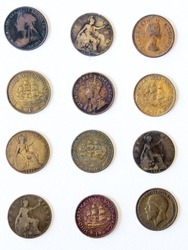 Various old, well-used South African pennies on a white background