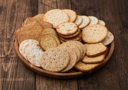 Various organic crispy wheat, rye and corn flatbread crackers with sesame and salt in round plate on wood background.