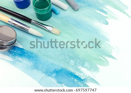 various paintbrushes, paints and pastel chalks on green blue watercolor background #697597747