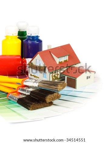 Various painting tools, miniature house and color guide on a white background - stock photo