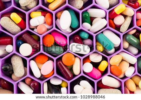 Various pills and capsules on cellular comb organizer tray as daily vitamins and supplements dosage routine concept