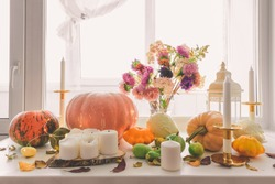 Various pumpkins, candles and a bouquet in a vase on the windowsill. Autumn decorations.