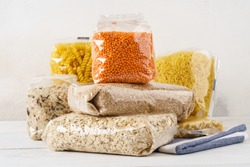 Various raw groats, cereal grains and pasta in transparent plastic bags on a kitchen table. Ingredients for cooking.