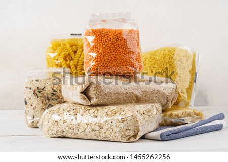 Various raw groats, cereal grains and pasta in transparent plastic bags on a kitchen table. Ingredients for cooking. Stockfoto ©