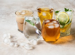Various refreshing drinks in glasses with ice. Apple juice, homemade lemonade, iced coffee, iced fruit tea and sparkling water on beige background. Copy space