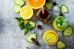 Various refreshments drinks - detox cucumber water, cherry juice and orange juice on stone table. Top view flat lay.