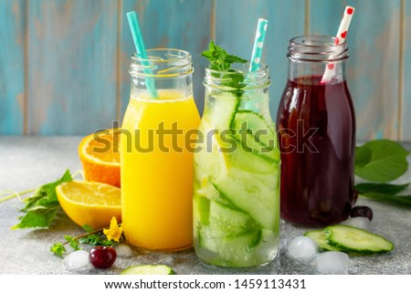 Various refreshments drinks - detox cucumber water, cherry juice and orange juice on stone table. #1459113431