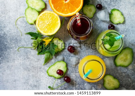 Various refreshments drinks - detox cucumber water, cherry juice and orange juice on stone table. Top view flat lay. #1459113899