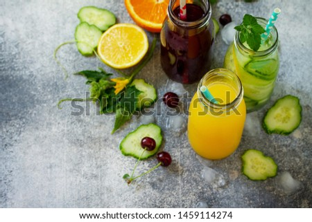 Various refreshments drinks - detox cucumber water, cherry juice and orange juice on stone table. Top view flat lay with copy space for your text. #1459114274