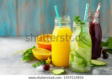 Various refreshments drinks - detox cucumber water, cherry juice and orange juice on stone table. Copy space for your text. #1459114856